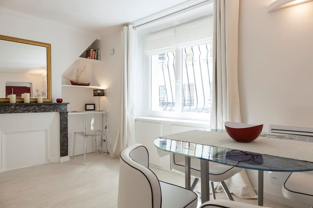 White walls & cream-colored wooden floor add even more light & space and sets a relaxed ambiance. Ancient marble fireplace is purely décorative,  next to it a work desk, a shelf, and a small cabinet.