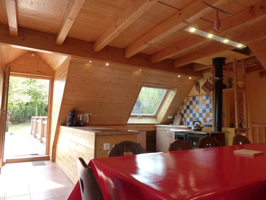 Espace de vie lumineux avec une cuisinière à bois, une plaque de cuisson à induction, un four électrique et un frigo,  et un accès direct sur le pré