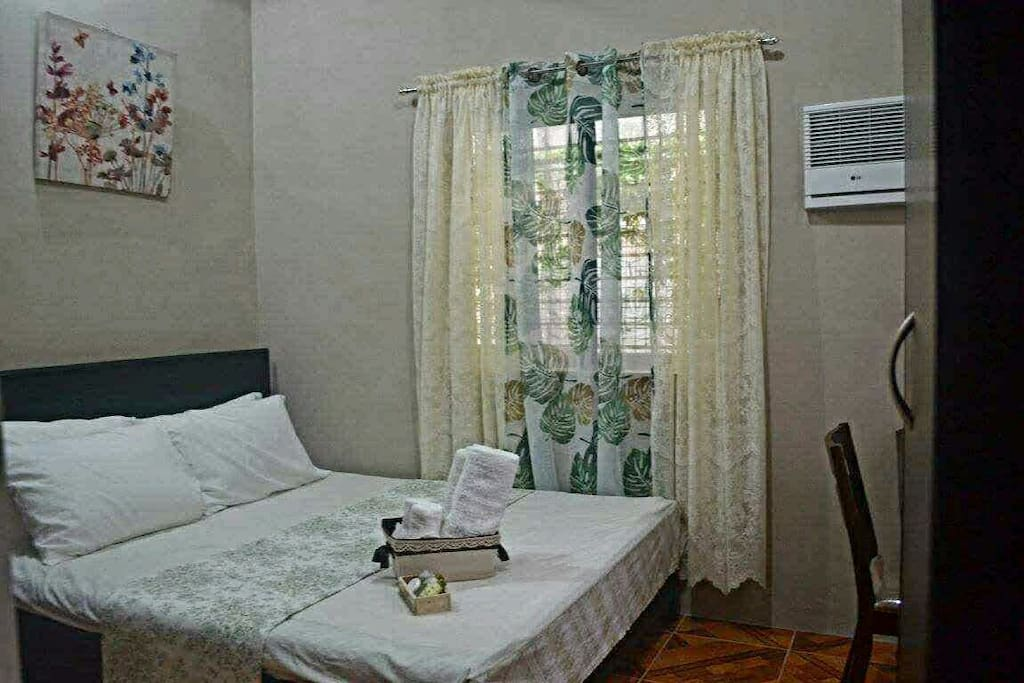 Room with queen-sized bed, wardrobe cabinet and study desk.