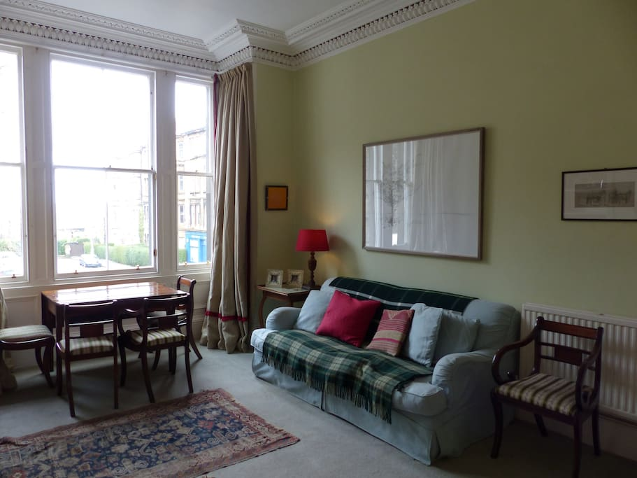 Comfortable, spacious sitting room with open outlook onto leafy  rooftop view.