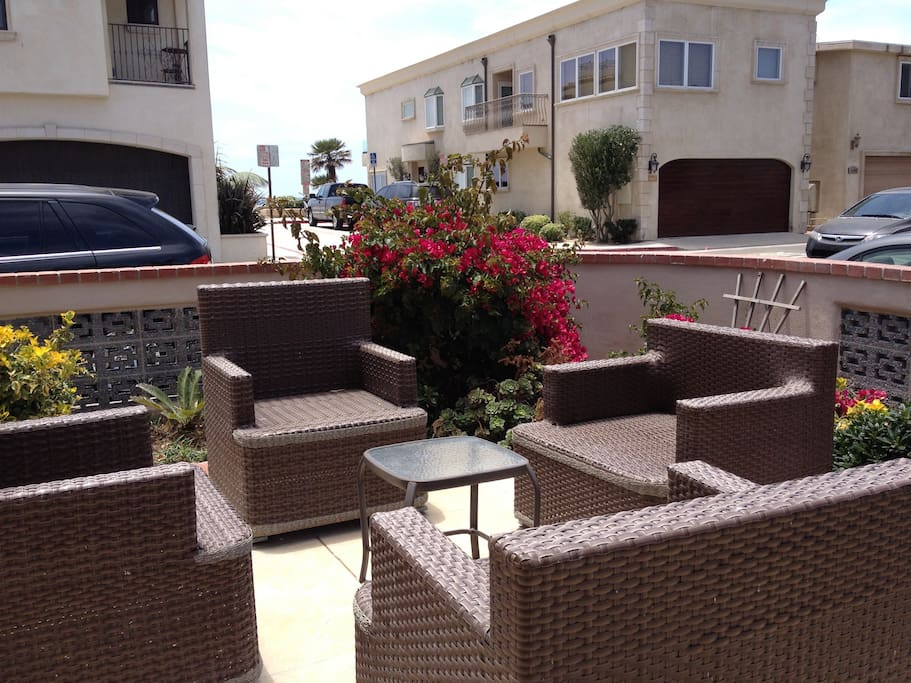 Patio with siting for ten or more, outside speakers, lounge chair, and umbrella.