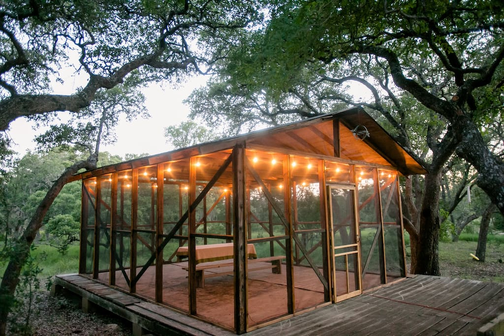 Screened in cabin is a peaceful outdoor gathering space.