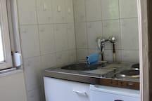 kleine Kitchenette mit Kühlschrank, Herd und Wasserkocher