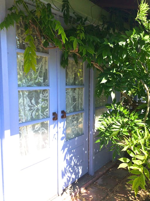 Enchanting french doors along the front of the cottage-- these open up to a patio with a fountain.