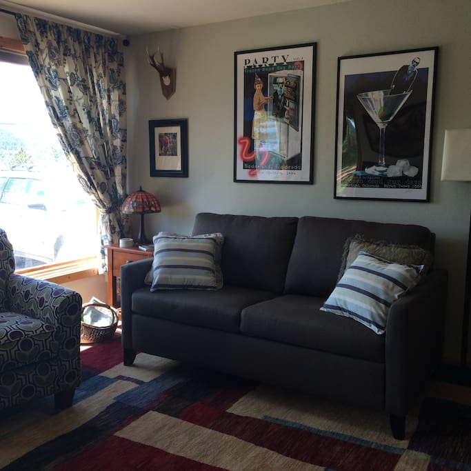 This is the living room area with two Large windows positioned toward the view over town. This couch makes a queen sleeper bed of top quality. It has a gel mattress that works to cool you when you're hot and warm you when you're cold.