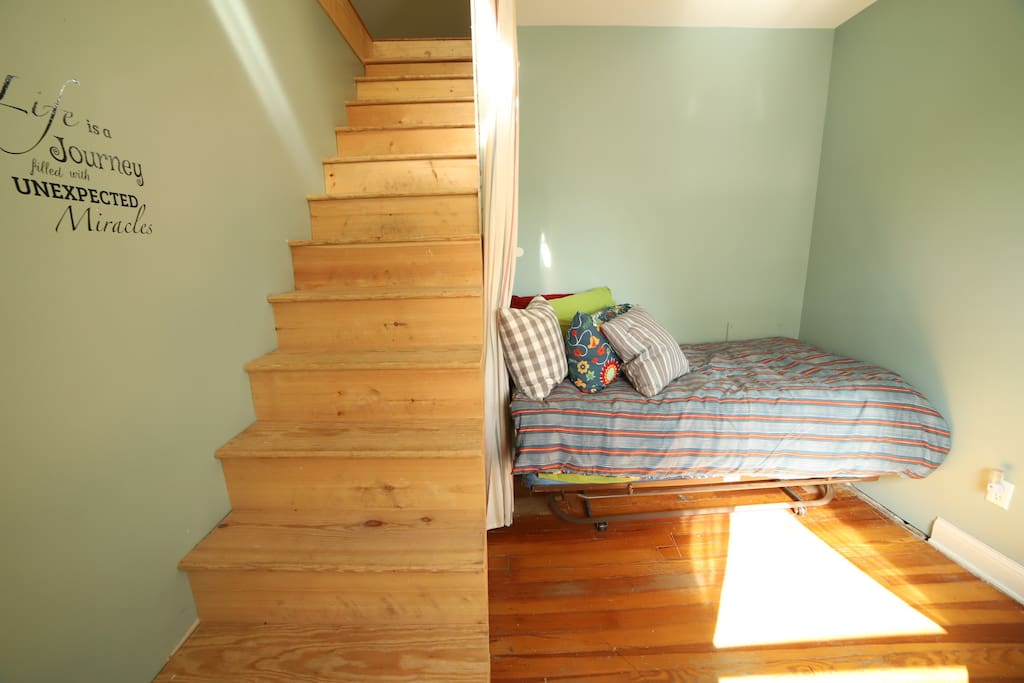 This is a walk through room with curtains that can be pulled to block off the stairs and provide full privacy. The stairs lead to a room in the attic.