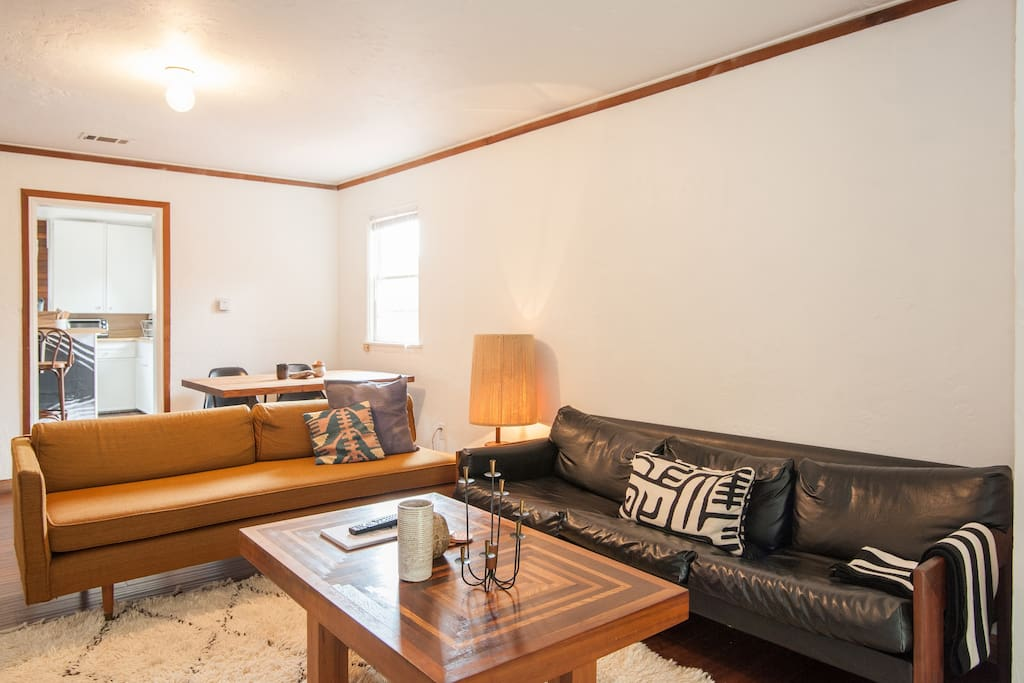Main / Living room has an open layout with dark wood floors and natural light.  2 couches for lounging in front of the tv/entertainment center with a view to the front yard.  Mid century style rust-colored sofa is also a daybed and comfortably sleeps 1