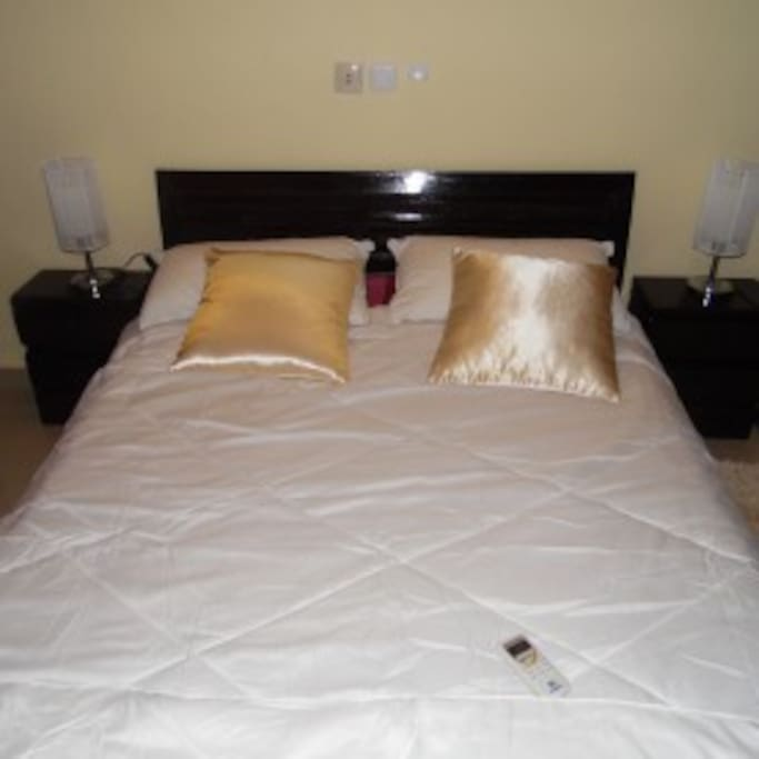 Chambre disposant d'un lit de deux places avec deux lampes de chevets  et une grande penderie