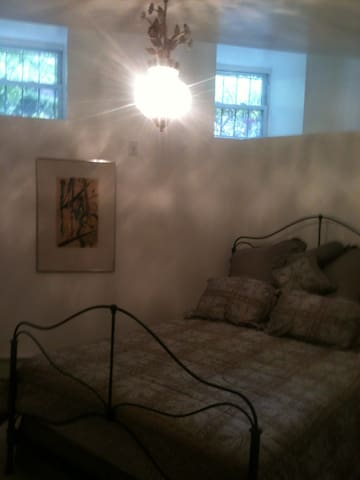 View of bedroom's queen sized bed, wall painting, chandelier, windows