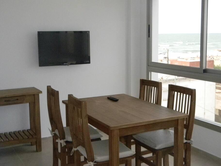 La misma habitación  tomada del otro extremo donde se ve la mesa, el televisor y la vista al mar.