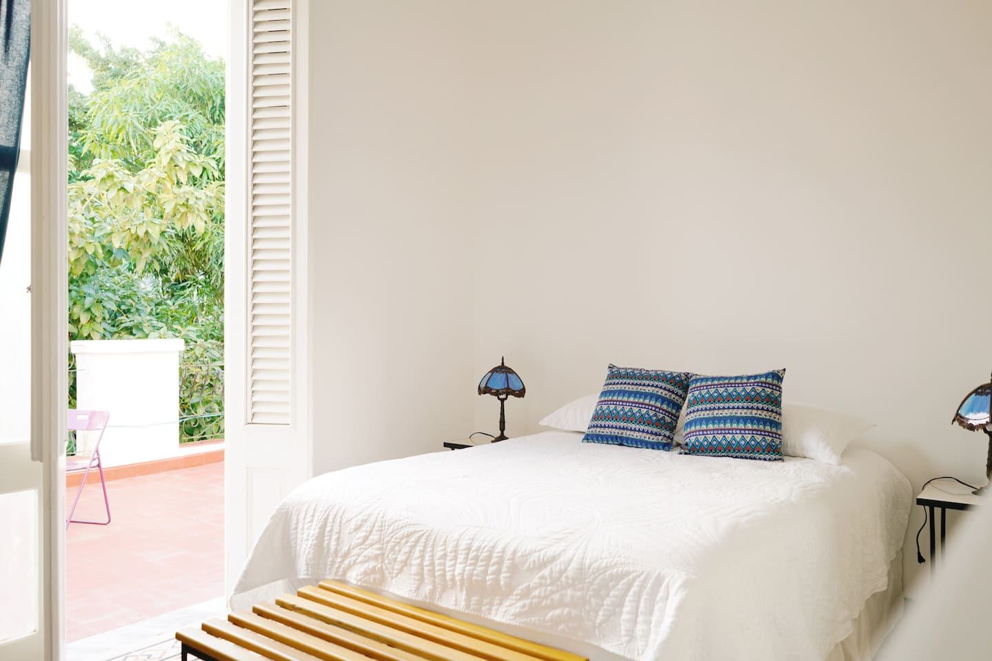 A luxury queen room with french doors leading to balcony with garden view to enjoy a morning cuban coffee and peaceful surroundings.