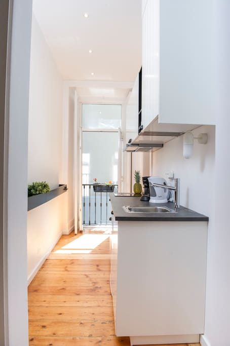 Kitchen with fridge, microwave, toaster, tea kettle, coffee machine; dishes & cutlery