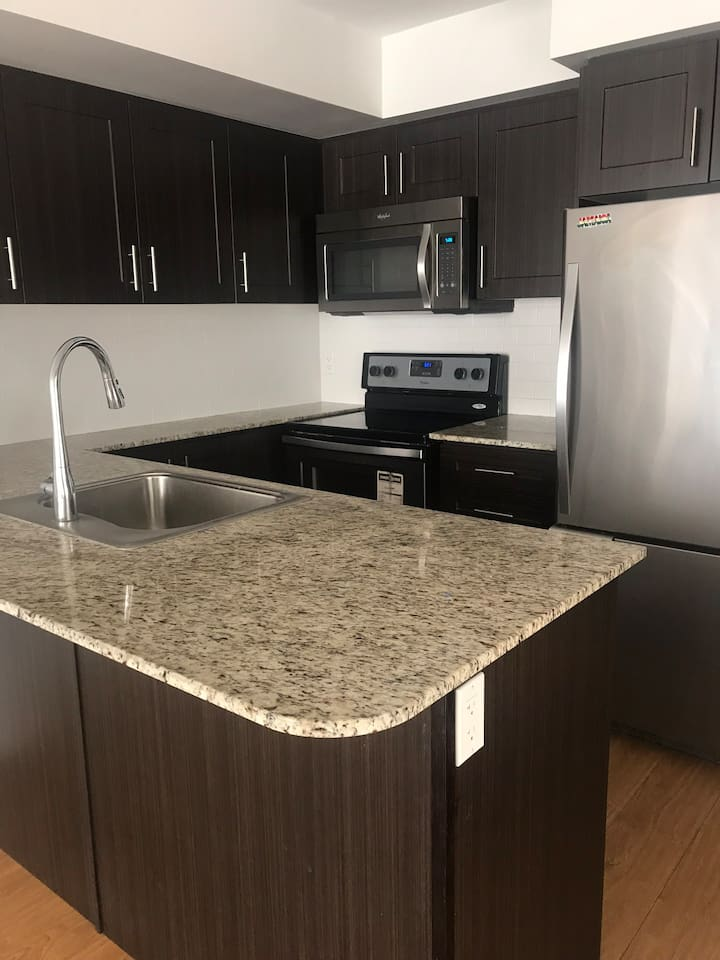 Full granite countertops with kitchen peninsula sink and large prep areas . Large fridge / freezer . Ceramic stove-top range /stove below.  Combo microwave and exhaust range hood above stove.