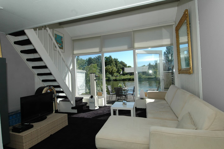 Sfeervolle woonkamer met toegang tot het terras en uitzicht op de vecht