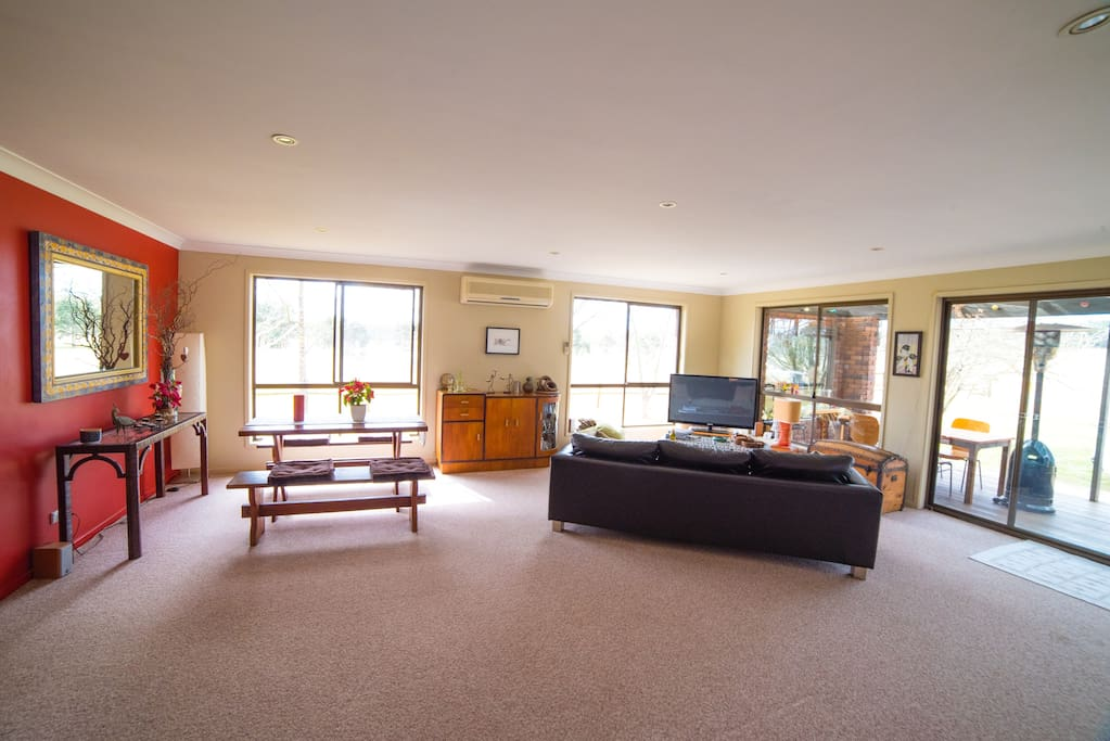 Lounge/dining area with large windows overlooking the paddocks