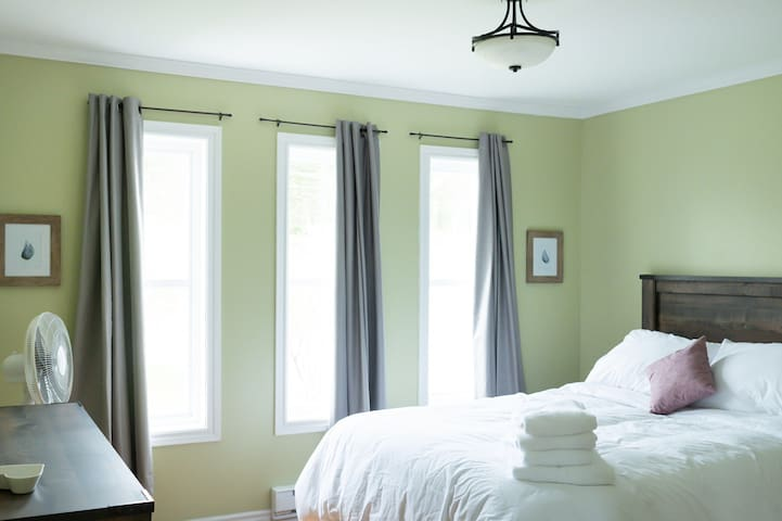 The master bedroom has a comfortable queen size bed (all of our linens are Hotel quality bedding from True North), a spacious closet for hanging your clothes, a dresser, and a suitcase rack so you can make yourself right at home.