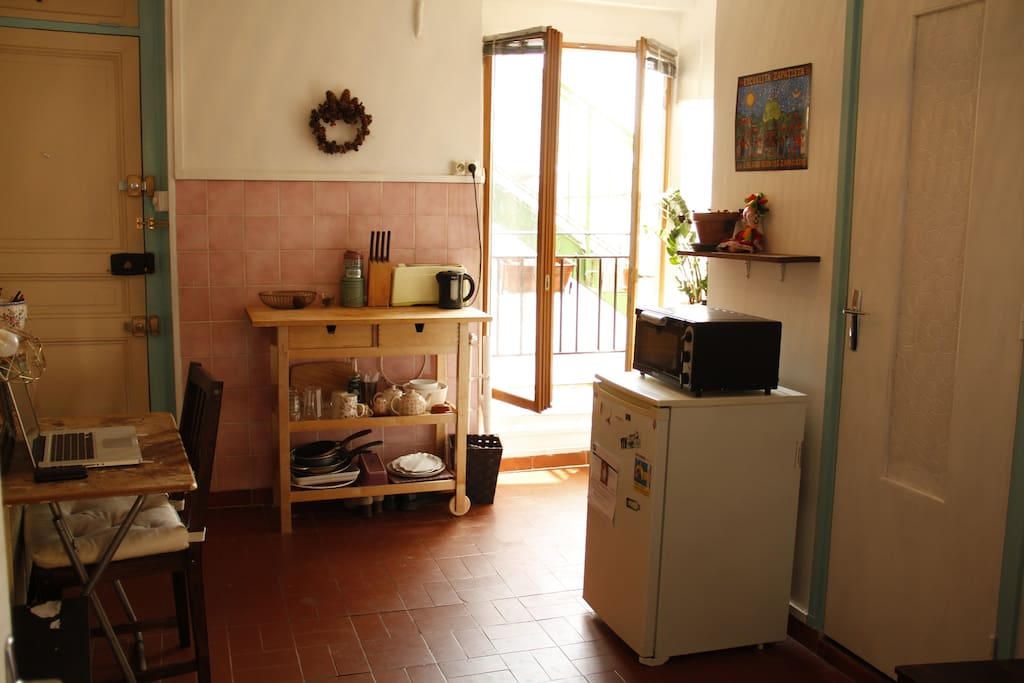 This is a large view of the kitchen. You have a small desk to work, a refrigerator, a toaster, a water boiler, and a little oven.