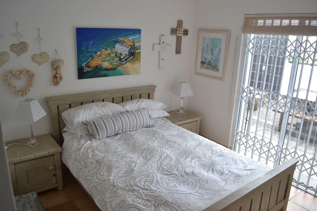 Double bed with built in dresser and cupboards. Sliding door opens on to private garden. Security door.