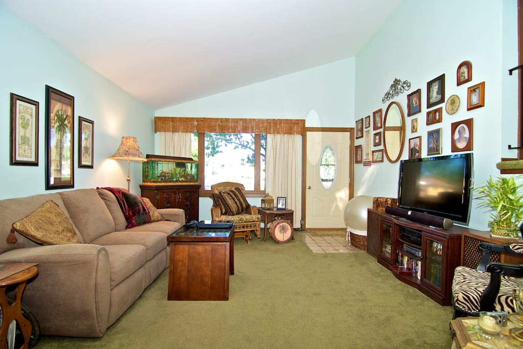 The living room with flat screen tv and tropical fish tank.