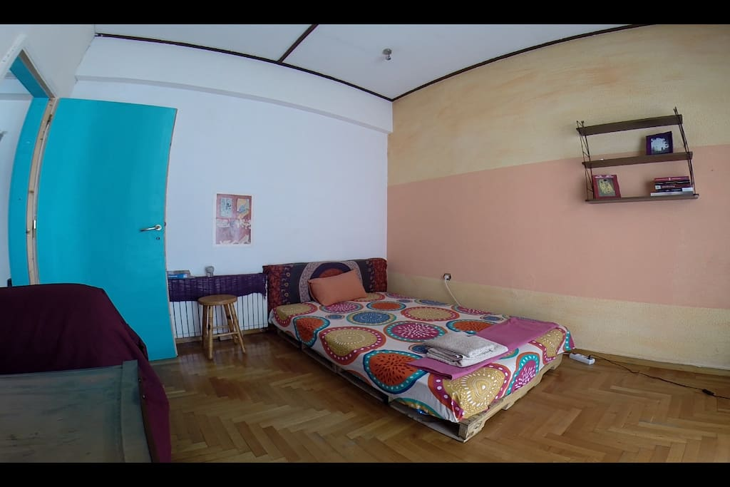 another perspective of the room with a double bed, desktop, closet, space and sun!