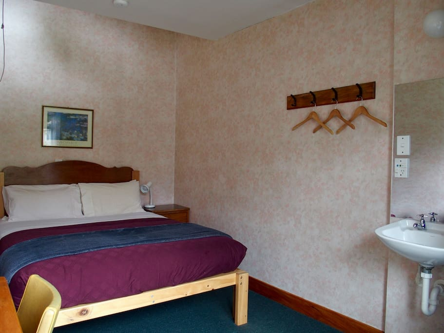 Double room with shared facilities. Sink and desk in the room.