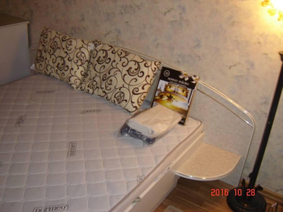 Спальная с двухспальной кроватью с торшером со встроенным платяным шкафом с зеркальными дверьми.