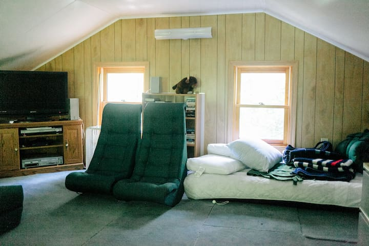 The attic loft with additional beds (air mattresses), and another TV.