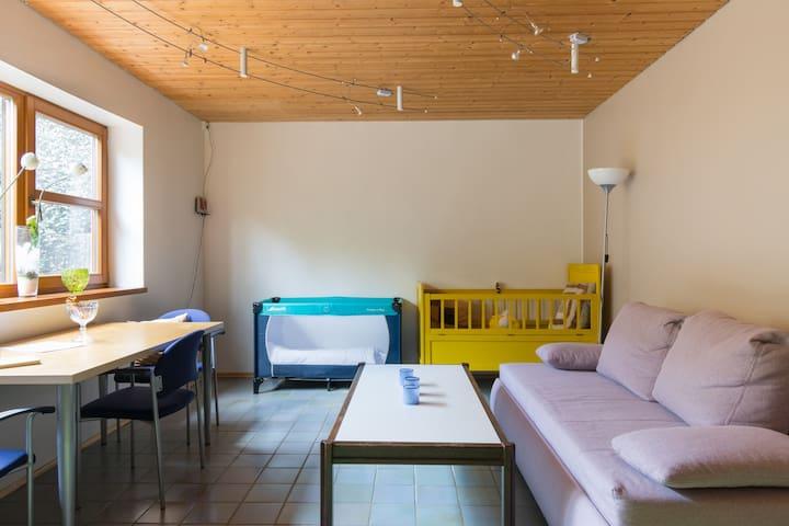 Wohnzimmer mit Esstisch , Couch ( ausziehbar) und 2 Kinderbetten