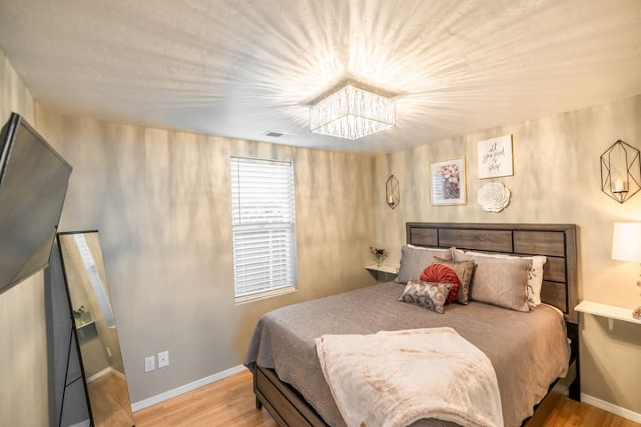 Bedroom with smart TV and queen size bed.