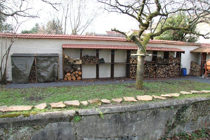 Une partie du jardin avec sa réserve de bois