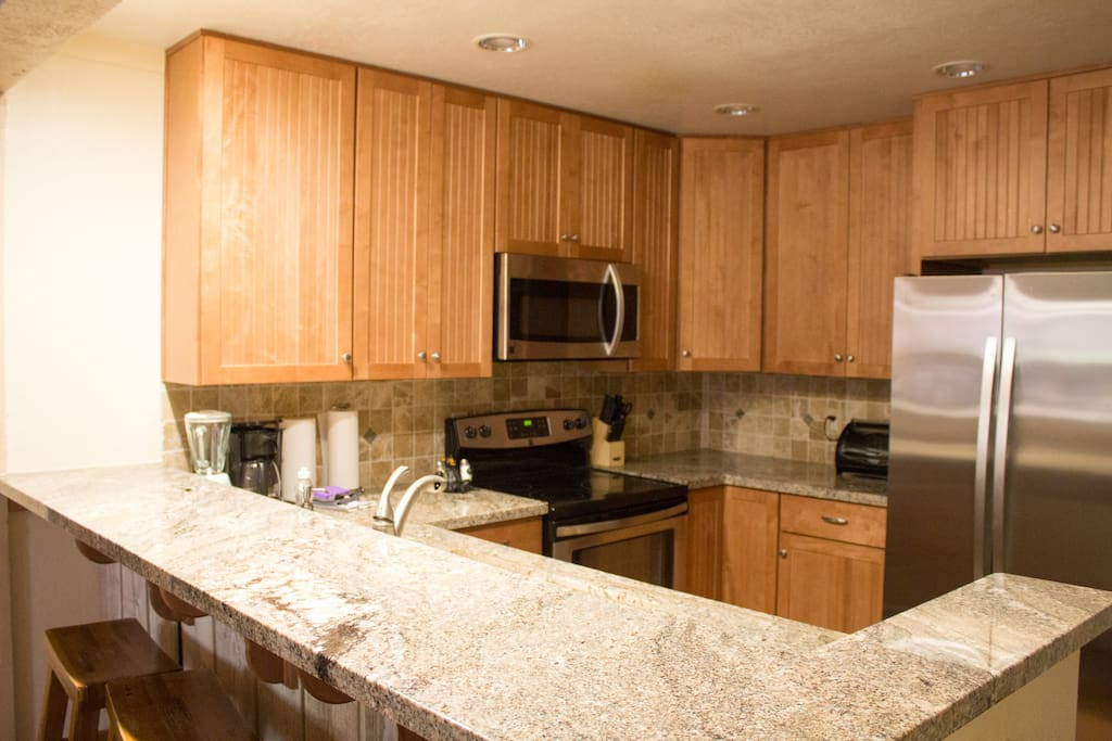 Full kitchen with stainless steel appliances and bar stools.