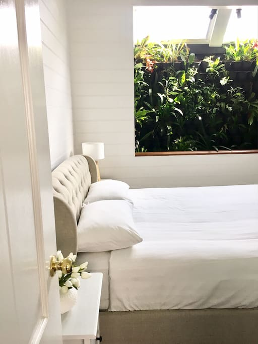 One our our main bedrooms featuring our infamous garden wall and queen bed.