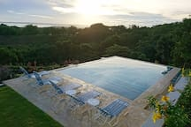 Saltwater pool with swim up bar and oversize steps with sweeping view of the Caribbean and Aguadilla Bay