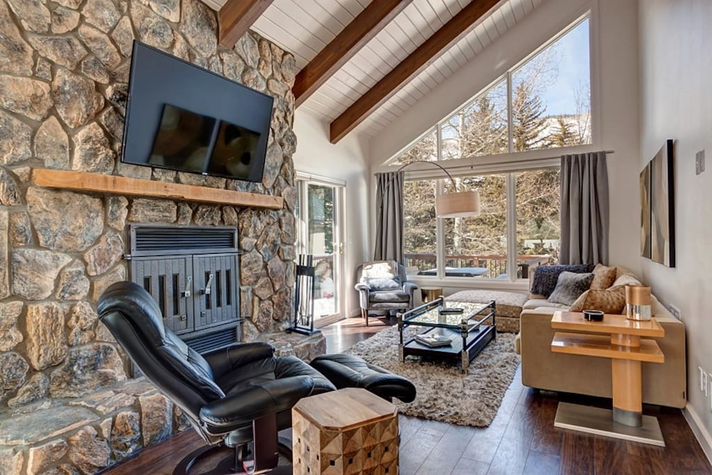 Fireplace with floor-to-ceiling stone surround and huge windows in the chic living area.