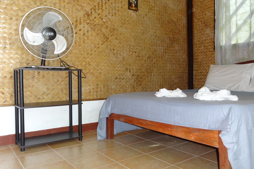 A comfortable double bed is accompanied by a fan and a shelf.