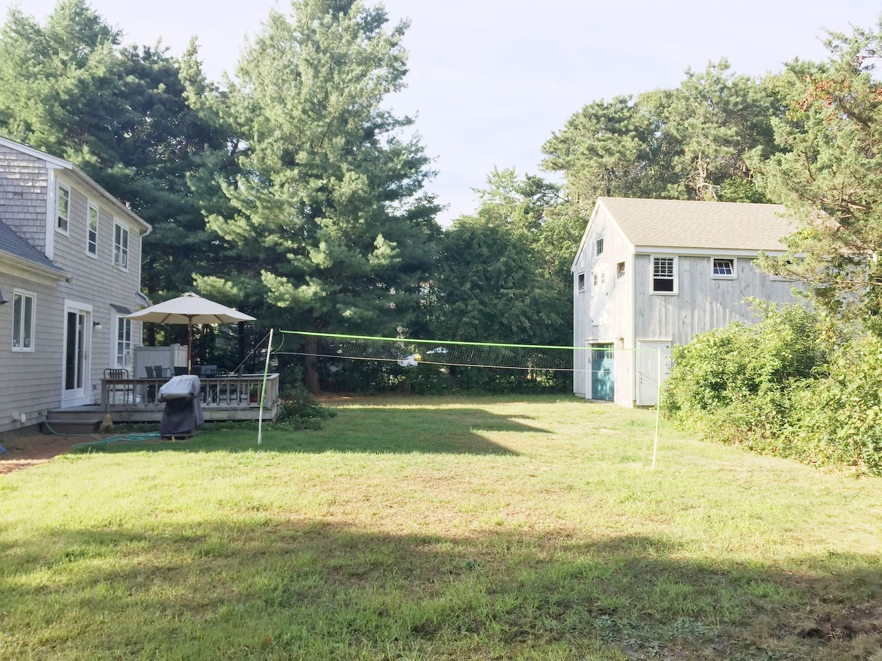 full back yard with outdoor barbecue, a volleyball net, hammock and loads of extra outdoor games in the tool shed.