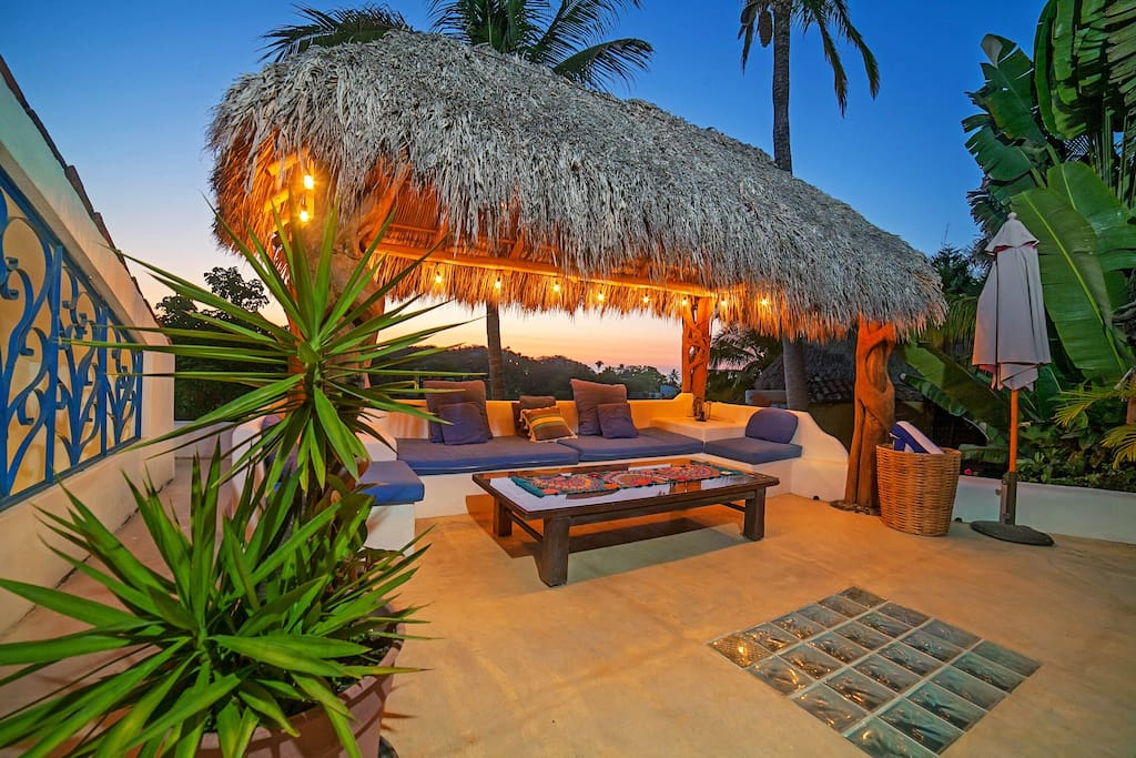 Poolside palapa at sunset with ocean views
