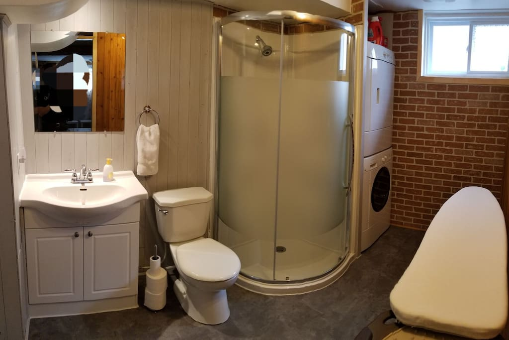 Full bathroom with washer and dryer in the basement.