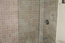 Main Shared bathroom walk in shower, toilet, sink & cabinet, opening window.