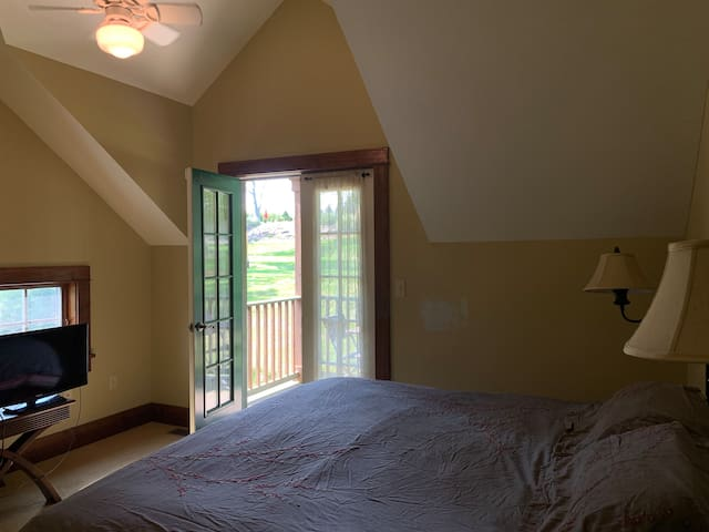 Master bedroom with king bed and balcony.