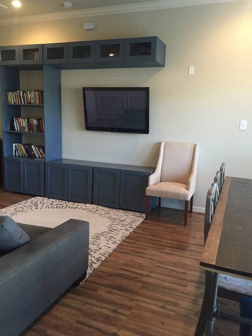 Living room features a mounted TV and custom built table.
