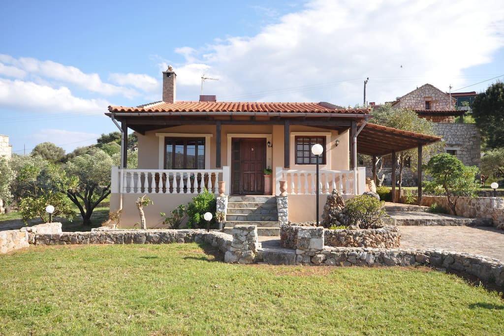 The outside of the house. It offers a spacious front yard with lawn, some olive trees and a parking space