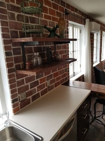 Wood plank shelves on vintage red brick wall.