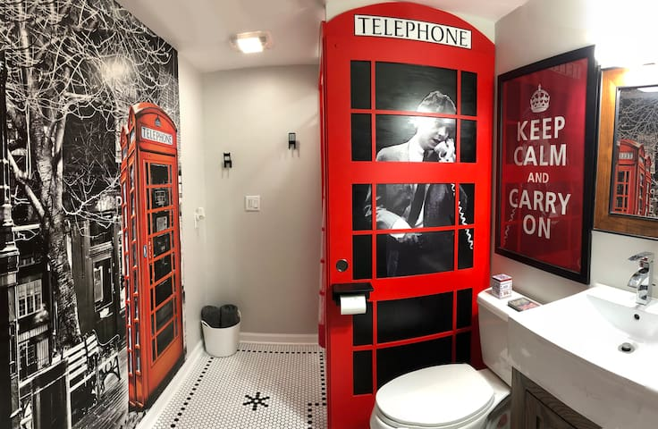 The London-themed bathroom features a red phone booth shower (with Paul McCartney on the phone!) and custom-designed hex tile floor.