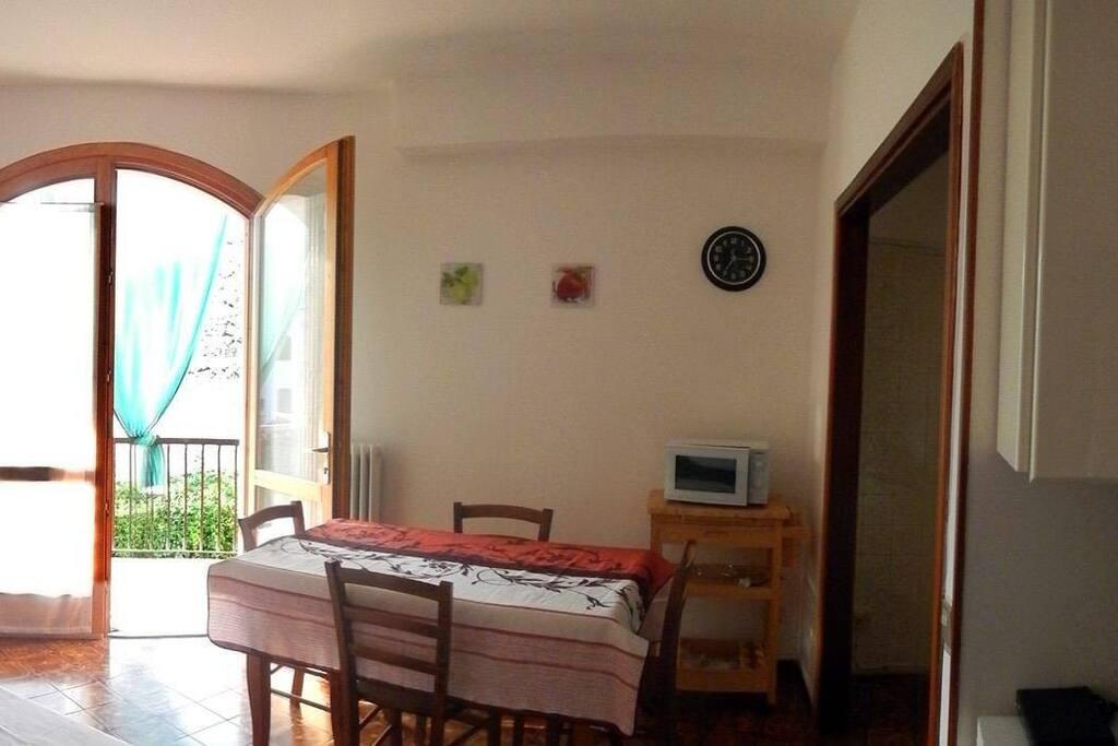 Sala da pranzo con cucina e divano letto