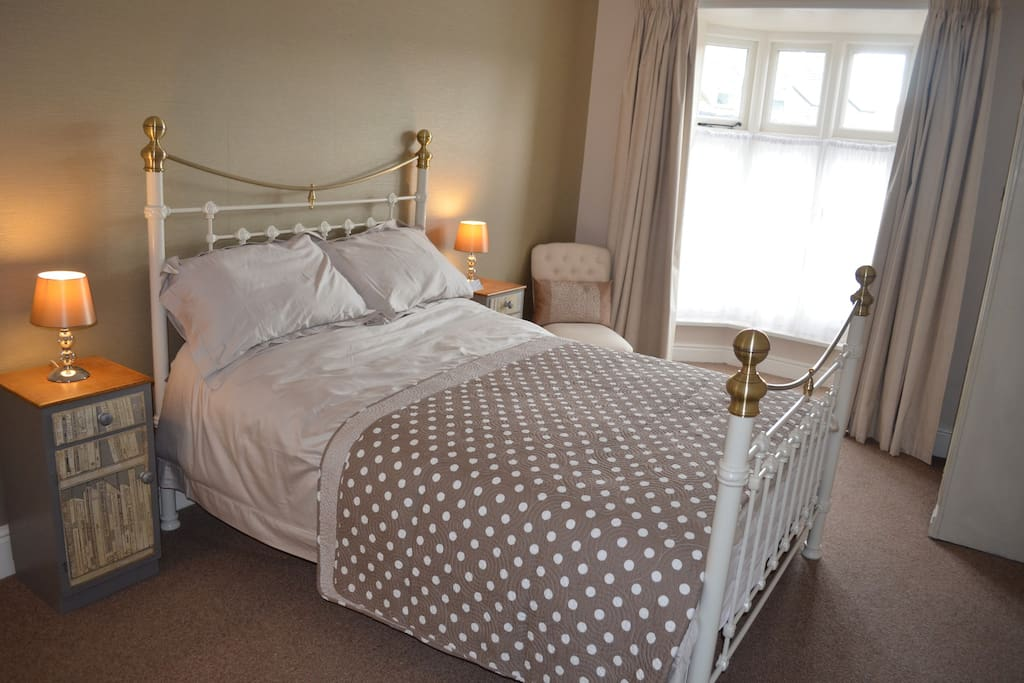 Master bedroom with double bed, wardrobe, chest of drawers, two side tables with lamps.