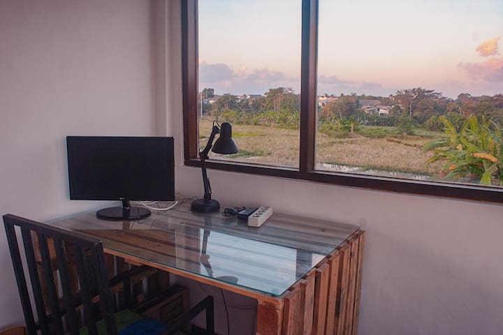 Working table with the view of rice fields. It is outside of the room to enjoy the ricefields views.