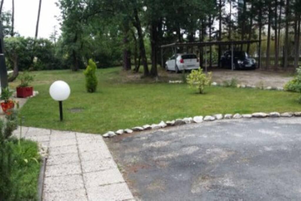 Le jardin avec parking goudronné  devant la maison.