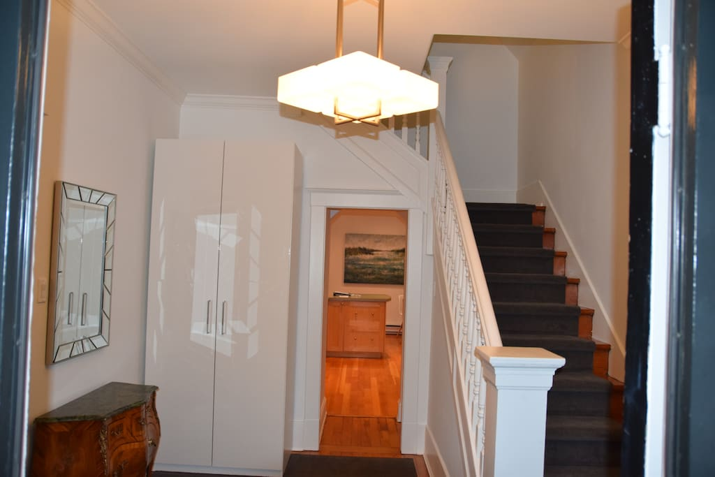 Charming spacious entrance with coat closet and staircase to bedrooms upstairs.