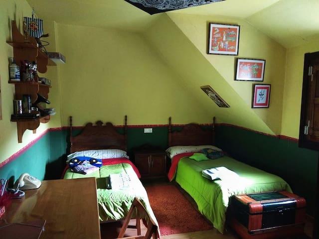 Cuarto con dos camas de 90cm y escritorio.